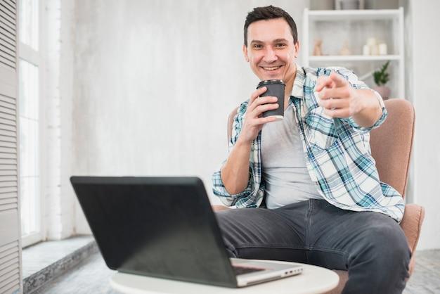 自宅のラップトップの近くの椅子に一杯の飲み物を保持笑みを浮かべて男 無料写真