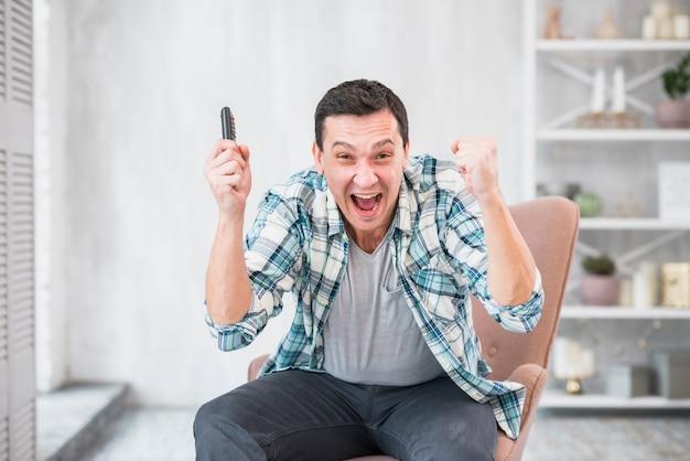 挙手で勝利したジョイスティックで興奮した若い男 無料写真