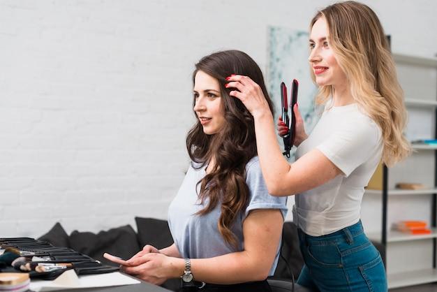 ヘアスタイリストの若い女性のためのカールを作る 無料写真