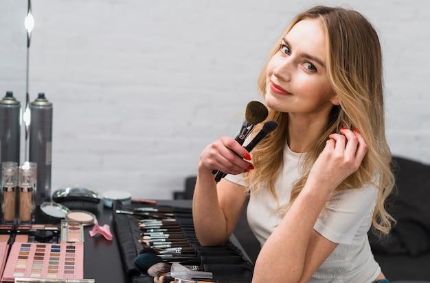 Молодая женщина, держащая макияж кисти, сидя в студии Бесплатные Фотографии