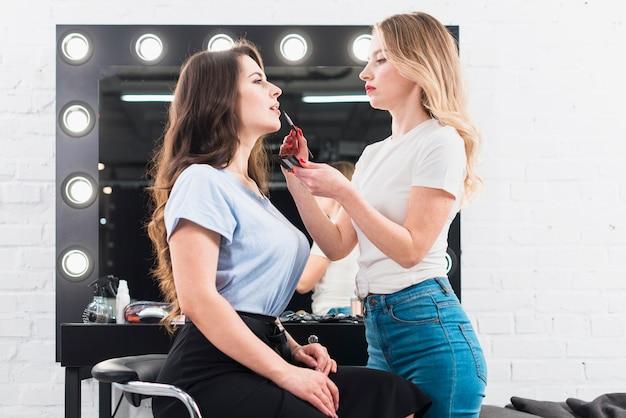 Женский визажист красит губы клиента Бесплатные Фотографии
