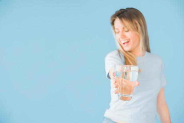 水のガラスを保持しているブロンドの女の子 無料写真