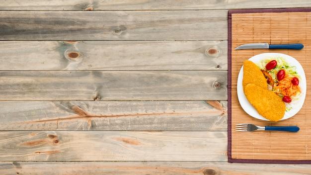 チキンの切り身と木製のテーブルの上の野菜サラダ添えプレート 無料写真