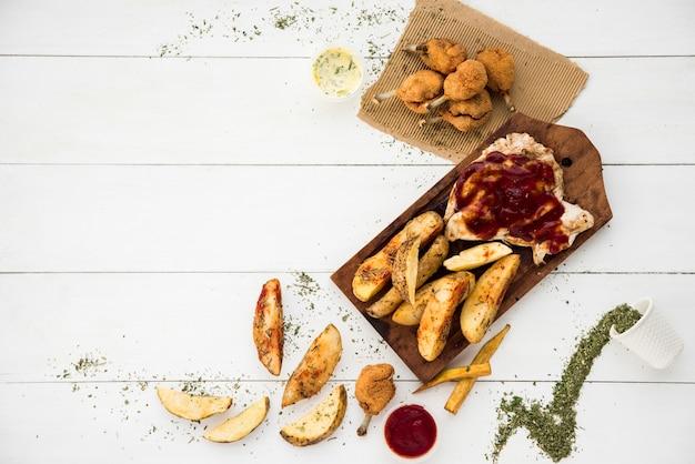 揚げ肉とジャガイモの周りのスパイス 無料写真