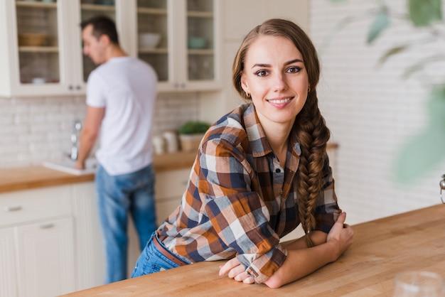 男が皿を洗っている間テーブルにもたれて笑顔の女性 無料写真