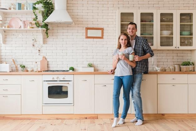 台所で休んでいるとお茶を楽しんでいる笑顔のカップル 無料写真