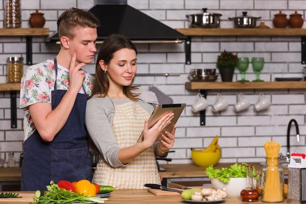 キッチンでタブレットのレシピを見て若いカップル 無料写真