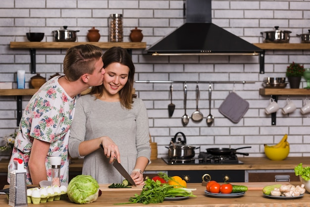 キッチンで料理のガールフレンドにキスをする男性 無料写真