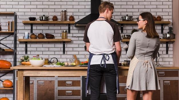 居心地の良いキッチンで調理する若いカップル 無料写真