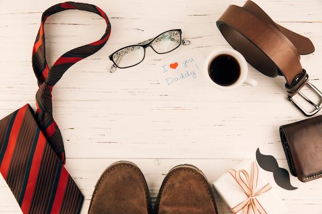 ギフトや飲み物のカップの近くの男性のアクセサリー間ブーツ 無料写真