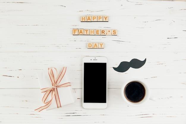 ギフトと一杯の飲み物を持つスマートフォンの近く幸せな父親の日言葉 無料写真
