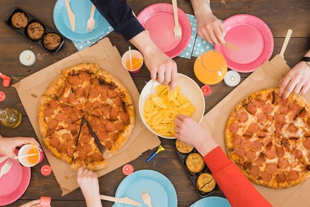 Друзья едят пиццу на вечеринке Бесплатные Фотографии