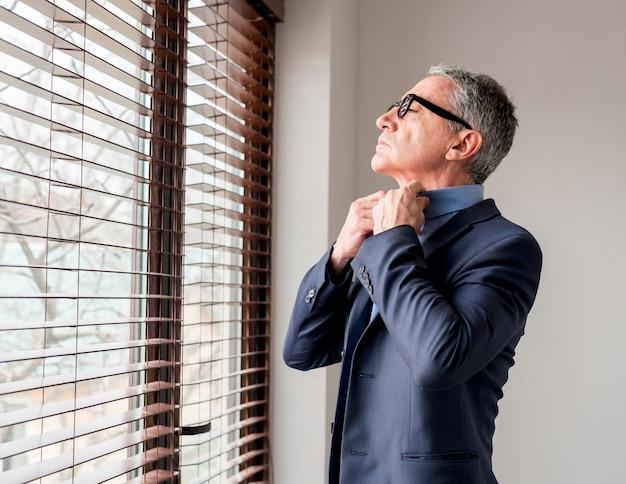 Пожилой бизнесмен смотрит в окно Бесплатные Фотографии