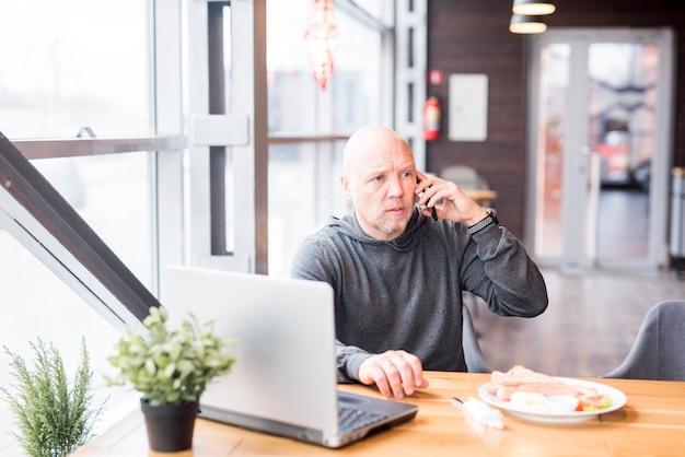 Пожилой мужчина разговаривает по мобильному телефону Бесплатные Фотографии