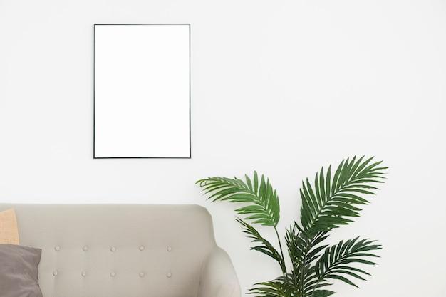 Декоративное растение с пустой рамой и диваном Бесплатные Фотографии