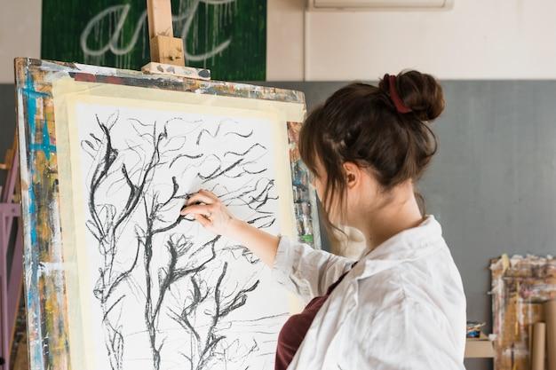 Женщина, рисование углем на холсте в мастерской Бесплатные Фотографии