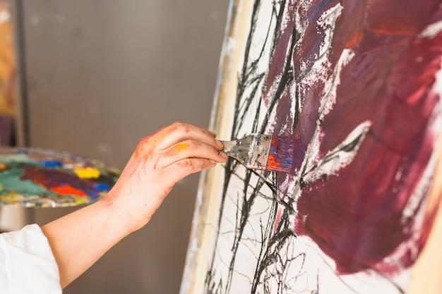 絵筆で芸術家の手の絵画のクローズアップ 無料写真
