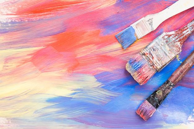 カラフルなブラシストロークと汚れたペイントブラシのトップビュー 無料写真