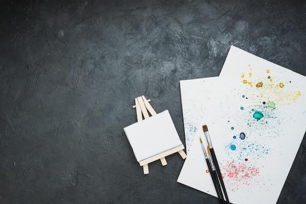 水彩画汚れ紙とミニイーゼルとペイントブラシの高角度のビュー 無料写真
