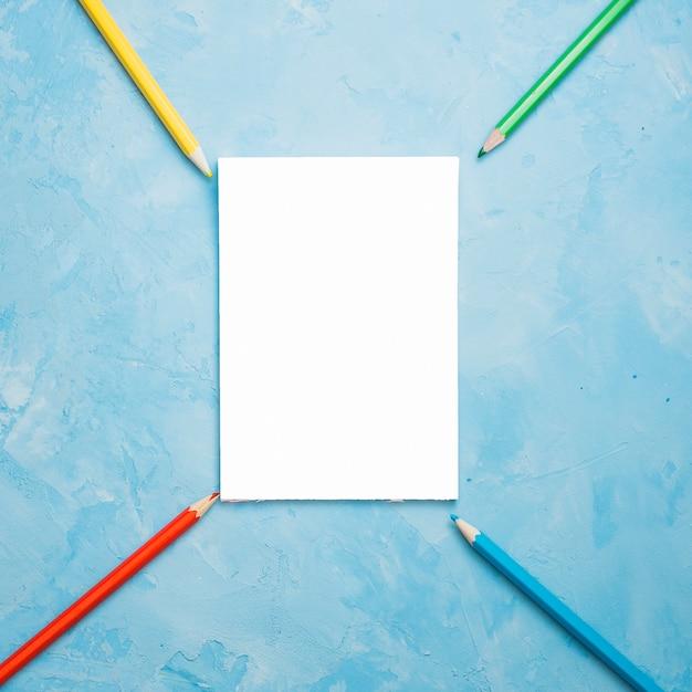 青い織り目加工の表面に白い空白のカードとカラフルな鉛筆の配置 無料写真