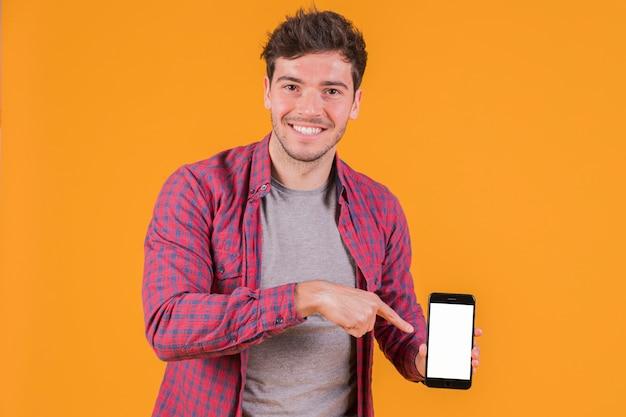 オレンジ色の背景に対して携帯電話で彼の指を指している笑顔の若い男の肖像 無料写真