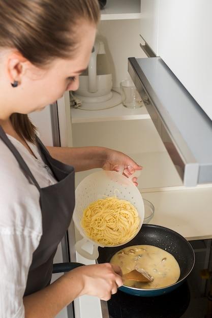 台所でスパゲッティを準備する若い女性の俯瞰 無料写真