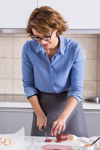 ピザを準備するためのナイフでサラミを切る若い女性の笑みを浮かべてください。 無料写真