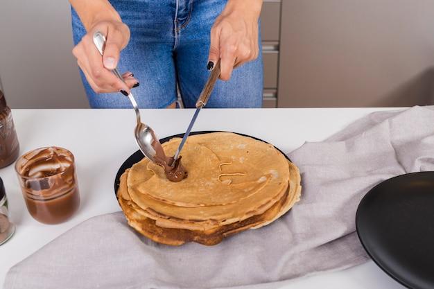 スプーンとナイフでパンケーキにピーナッツバターを広める女性のクローズアップ 無料写真