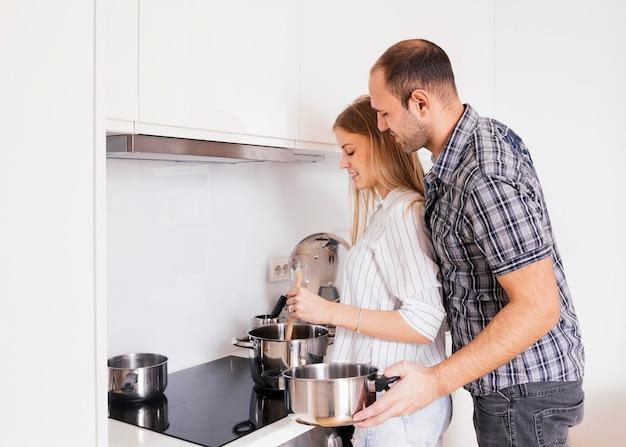 Прекрасная молодая пара готовит еду на современной кухне Бесплатные Фотографии