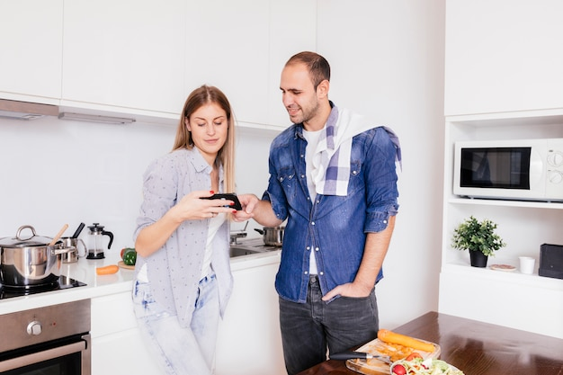 Молодая пара стоя на кухне с помощью мобильного телефона во время приготовления пищи Бесплатные Фотографии