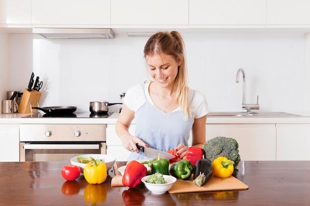木製のテーブルにナイフで新鮮な野菜を切る笑顔の若い女性の肖像画 無料写真