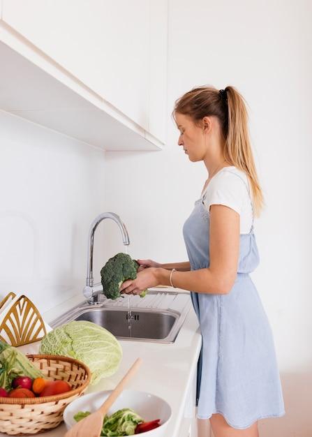 台所の流しにブロッコリーを洗う若い女性の側面図 無料写真