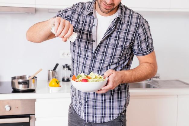 台所で料理をしながら野菜のサラダに塩を追加する若い男のクローズアップ 無料写真
