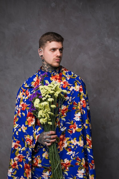 耳と紫と黄色のリモニウムの花を手で押し鼻を持つ若者の肖像 無料写真