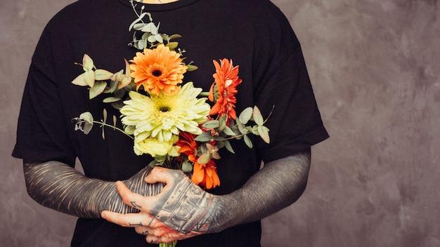 ガーベラの花束を持っている彼の手に入れ墨をした男の半ばセクション 無料写真