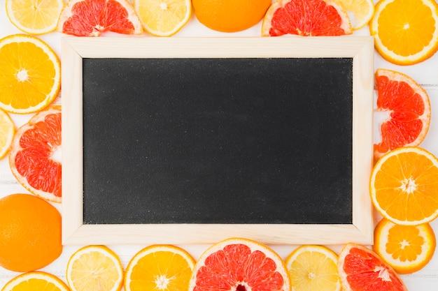 新鮮なグレープフルーツとオレンジの間の黒板 無料写真