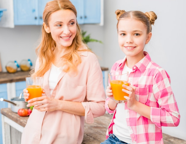 Портрет матери и дочери, держа в руке стакан сока Бесплатные Фотографии