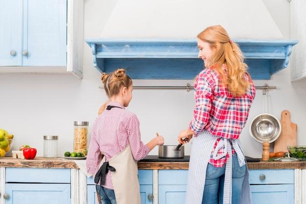 母と娘が台所で料理を調理の背面図 無料写真