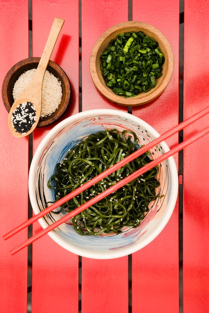 日本の中華海藻サラダの上のお箸とゴマと赤玉ねぎ 無料写真