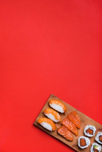 赤の背景にまな板の上のサーモン巻き寿司 無料写真