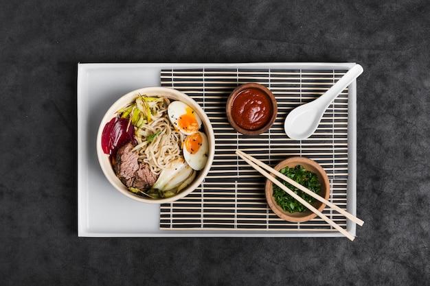 Азиатская лапша рамен с яйцами; салат; соус и зубок чеснока на белом подносе на фоне черной текстуры Бесплатные Фотографии