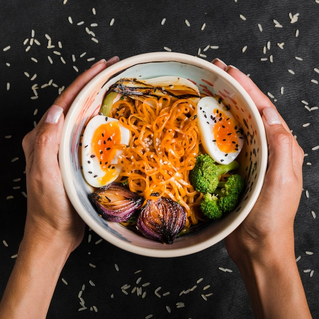卵と麺のボウルを持っている女性の手のクローズアップ。玉ねぎ;黒の背景上にボウルにブロッコリー 無料写真