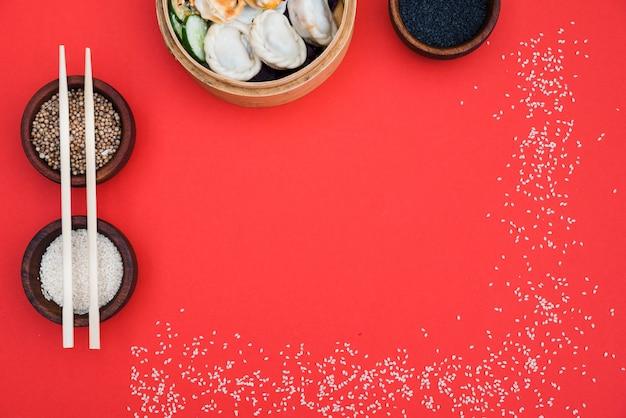 コリアンダーの種と蒸し器の餃子。赤の背景に黒と白のゴマ 無料写真