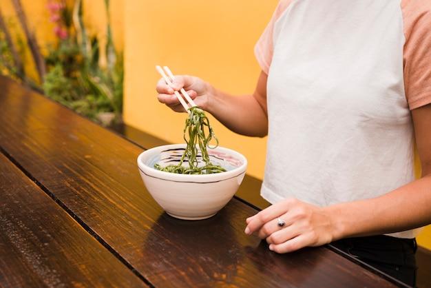 Крупным планом руки женщины, держащей водоросли с палочками для еды на деревянный стол Бесплатные Фотографии