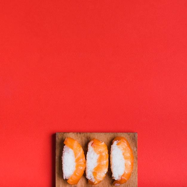 赤の背景にまな板の上のサーモンと古典的な寿司の俯瞰 無料写真