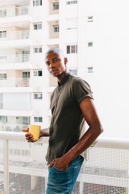 黄色のコーヒーカップを手で押し、バルコニーに立っているアフロの若い男の肖像 無料写真