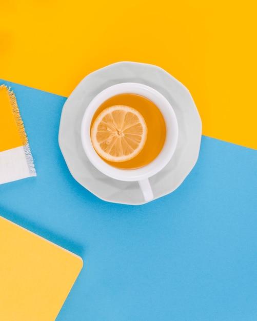 黄色と青の背景にレモンとジンジャーティーのカップ 無料写真