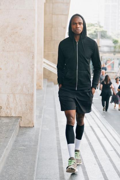 屋外の階段の近くを歩いて黒いパーカーのオスの運動選手の肖像画 無料写真