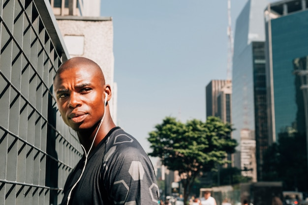 街で彼の耳の中にイヤホンを持つ深刻な若いフィットネス男の肖像 無料写真
