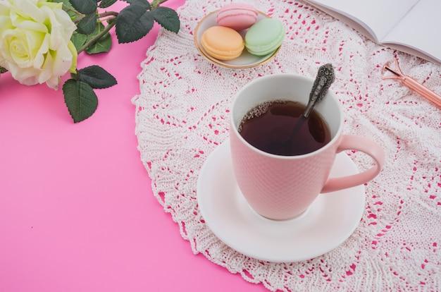 ピンクの背景にレースのテーブルクロスにマカロンとピンクのティーカップ 無料写真